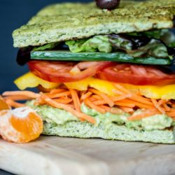 Broccoli Flatbread Sandwich with smashed avocado, shredded carrots, sliced yellow pepper, sliced tomatoes, vertical sliced english cucumber, Boston red lettuce