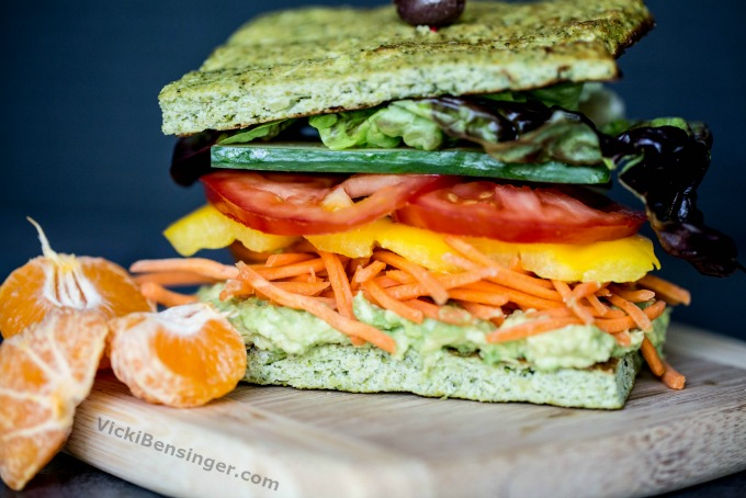 Broccoli Flatbread Sandwich with layered fresh veggies of smashed avocado, shredded carrots, sliced yellow peppers, sliced tomatoes, vertically sliced cucumber, and Boston red leaf lettuce