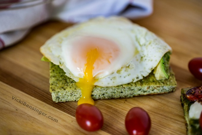 Broccoli Flatbread topped with sliced avocado topped with a sunny side up egg