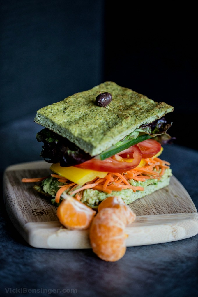 Broccoli Flatbread sandwiched between layers of smashed avocado, shredded carrots, sliced yellow pepper, tomatoes, cucumber and Boston red lettuce