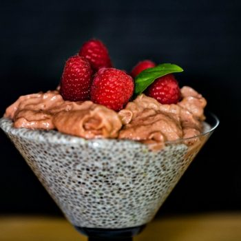 Chia Pudding topped with Raspberry Mousse and garnished with fresh raspberries with a sprig of basil