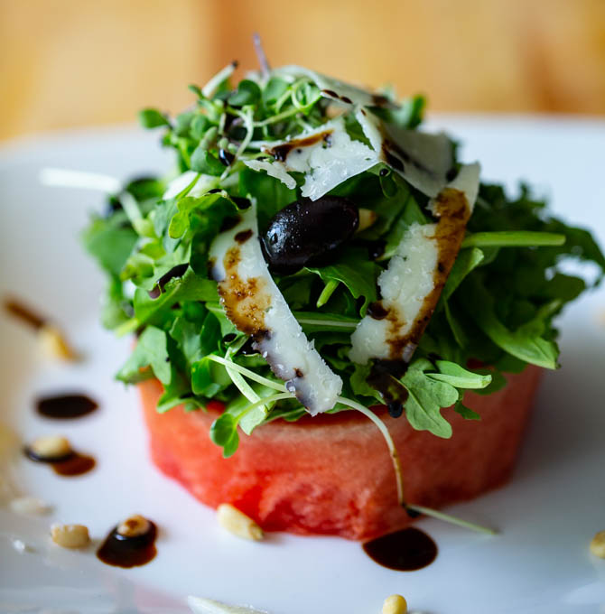 Watermelon Salad with Arugula, Pine Nuts, Pecorino Cheese, Kalamata Olives, & Balsamic Reduction