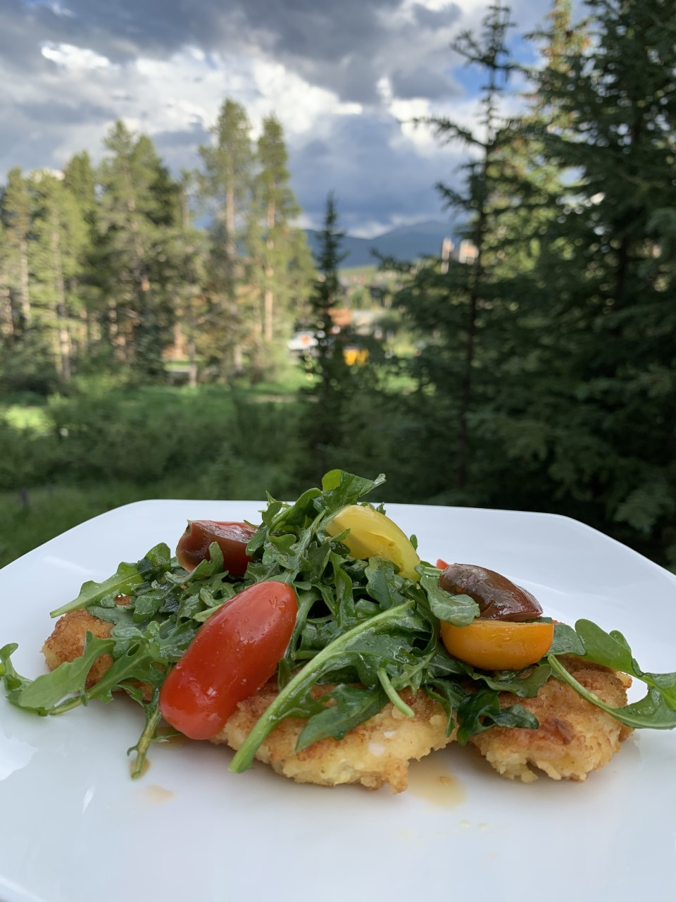 Thinly coated chicken breasts topped with an arugula & tomato salad