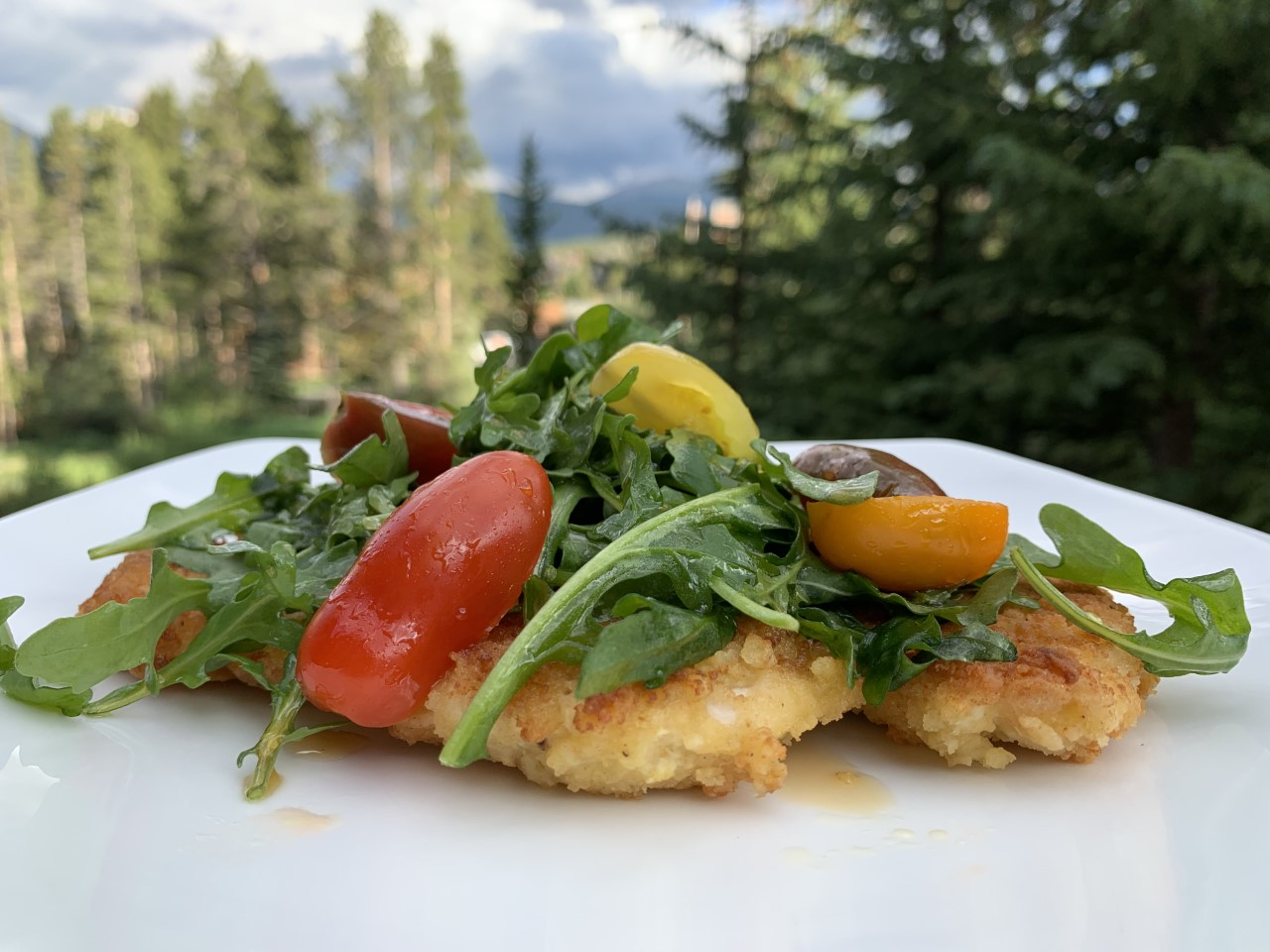 Chicken Milanese is a thinly coated chicken breast sauteed then topped with an arugula and tomato salad