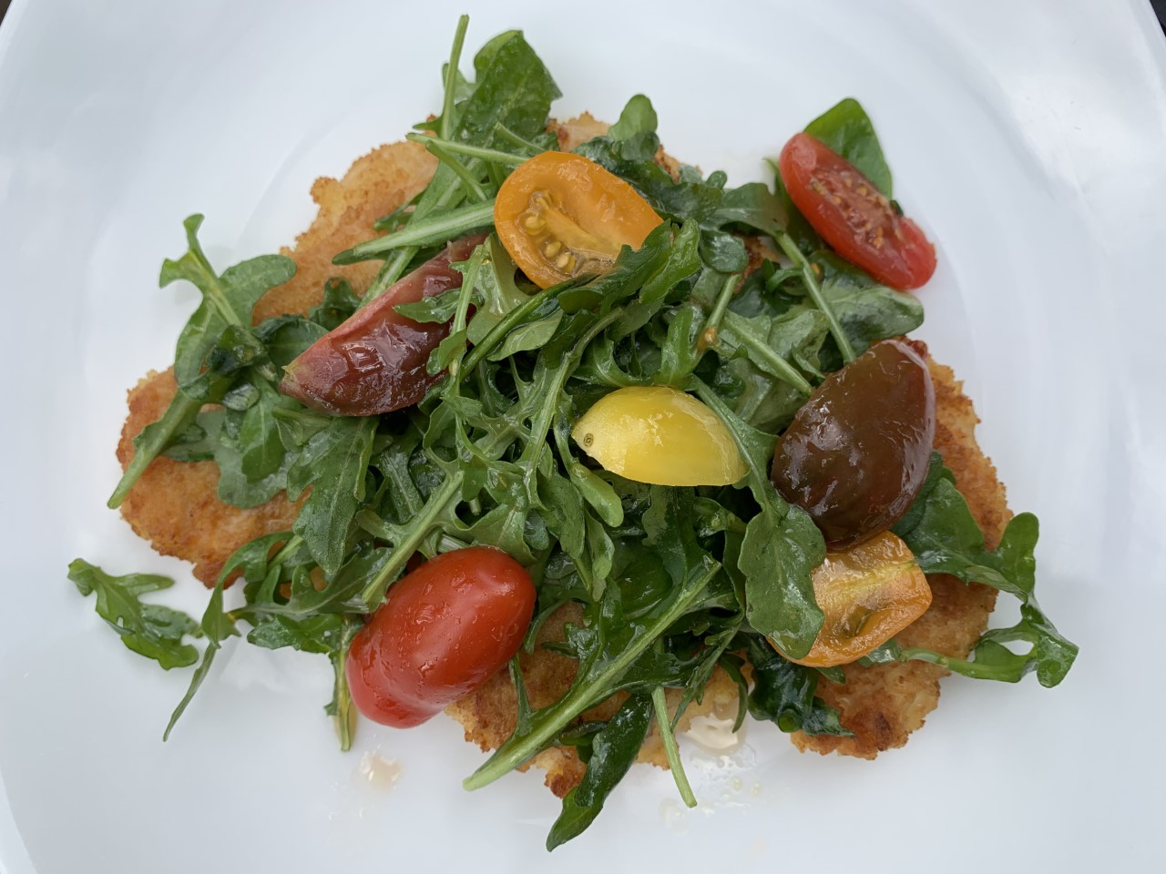 Chicken Milanese is thinly coated chicken breasts sauteed then topped with an arugula and tomato salad
