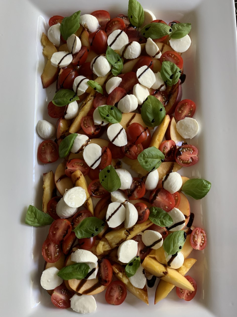 Grilled Peaches with mozzarella balls, tomatoes , basil, and balsamic reduction