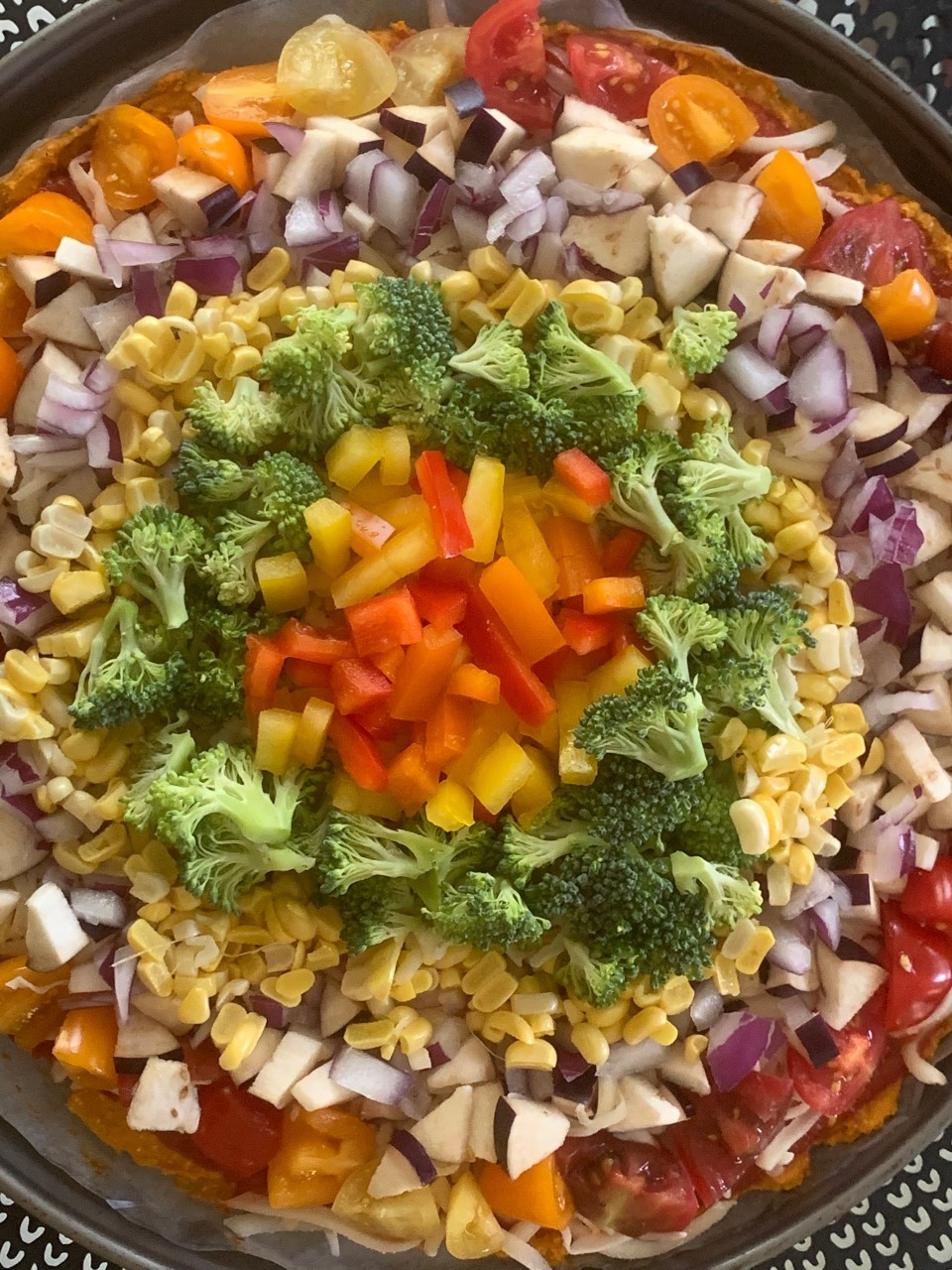 Rainbow Pizza with a sweet potato crust, bell peppers, onion, corn, butternut squash, eggplant, and broccoli