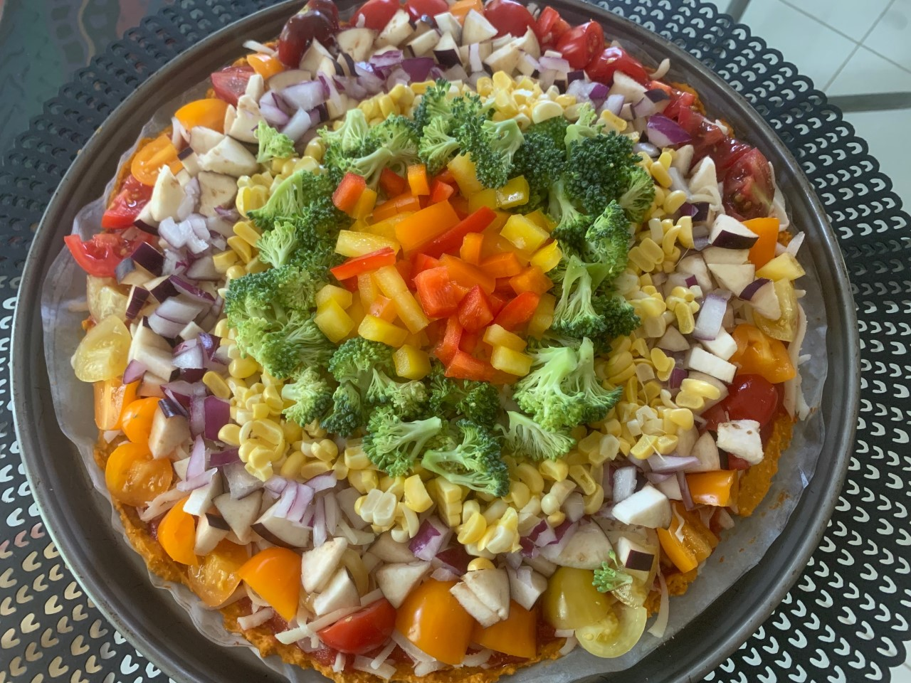 Rainbow Pizza with a sweet potato crust, bell peppers, corn, onions, butternut squash, eggplant, and broccoli