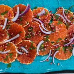 Orange and Pomegranate Salad with warm spices, slivered onions and pomegranate arils with a honey lime vinaigrette